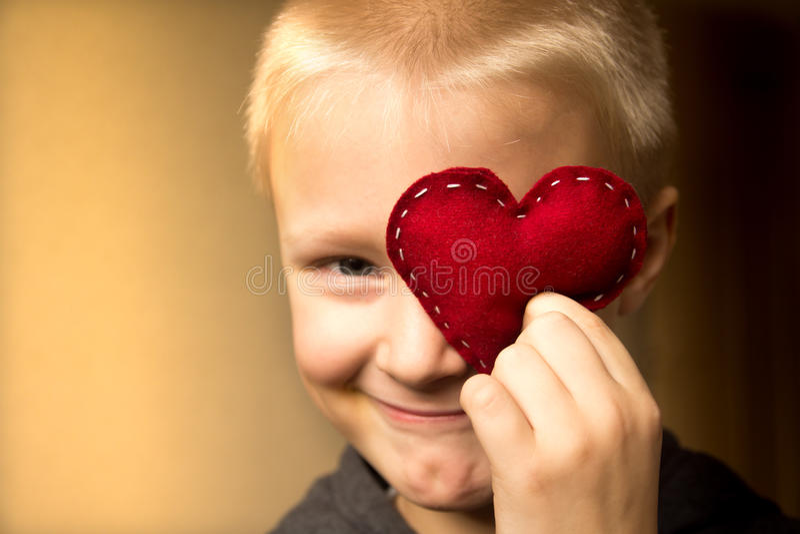 Lyckligt barn med röd hjärta fotografering för bildbyråer