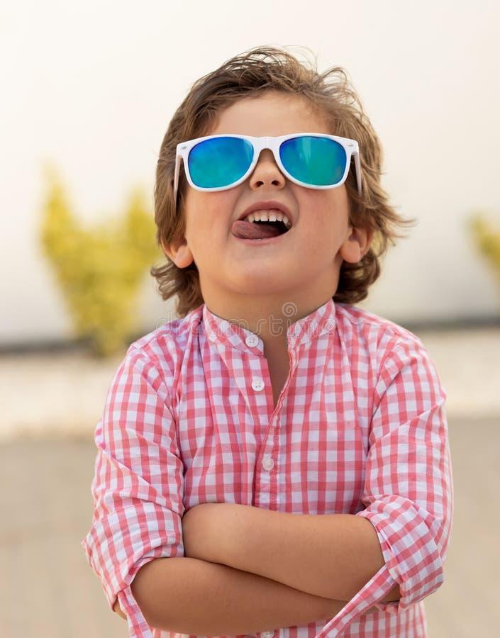 Lyckligt barn med solglasögon i trädgården arkivbild