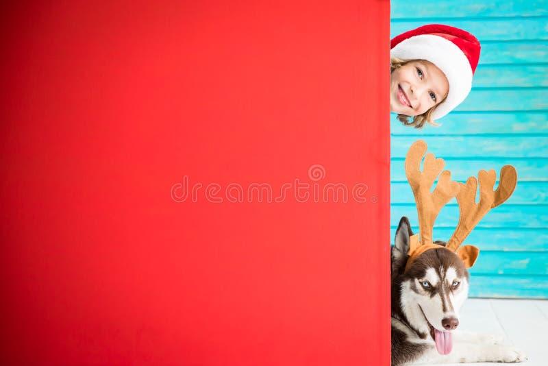 Lyckligt barn och hund på julhelgdagsafton royaltyfri foto