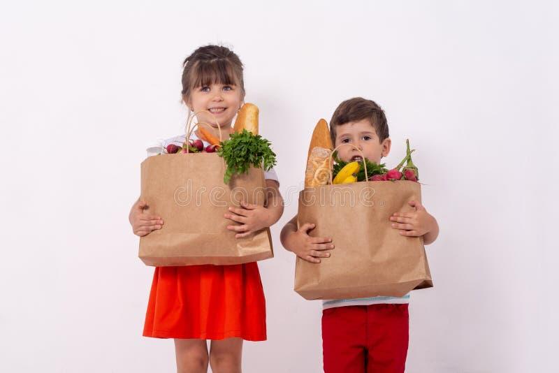Lyckligt barn och shoppingvagn Ungar som köper mat på livsmedelsbutiken eller supermarket Barn med grönsaker, bröd, mjölkar och a royaltyfri foto