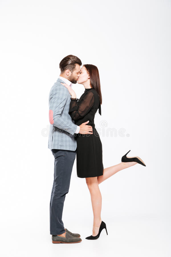 Lyckligt barn som älskar att kyssa för par som isoleras över vit bakgrund fotografering för bildbyråer
