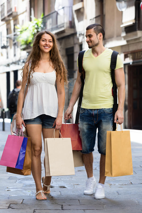 Lyckligt barn som älskar par med shoppingpåsar på staden fotografering för bildbyråer