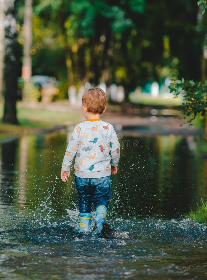 Lyckligt barn som går i pöl i gummistöveler tillbaka sikt arkivbild