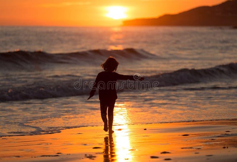 Lyckligt barn som kör på stranden under solnedgång arkivbilder