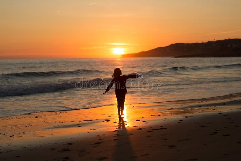 Lyckligt barn som kör på stranden under solnedgång royaltyfria bilder