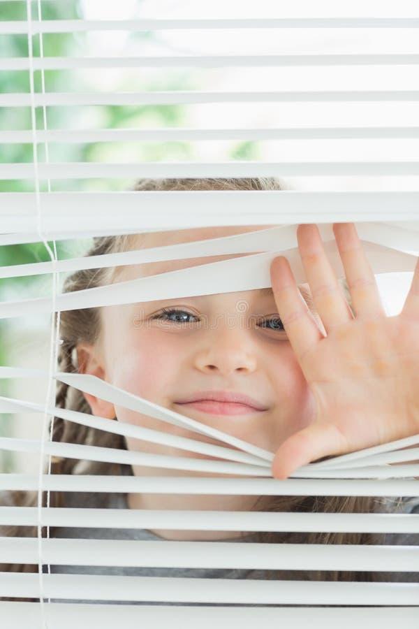 Lyckligt barn som kikar till och med rullgardiner arkivfoto