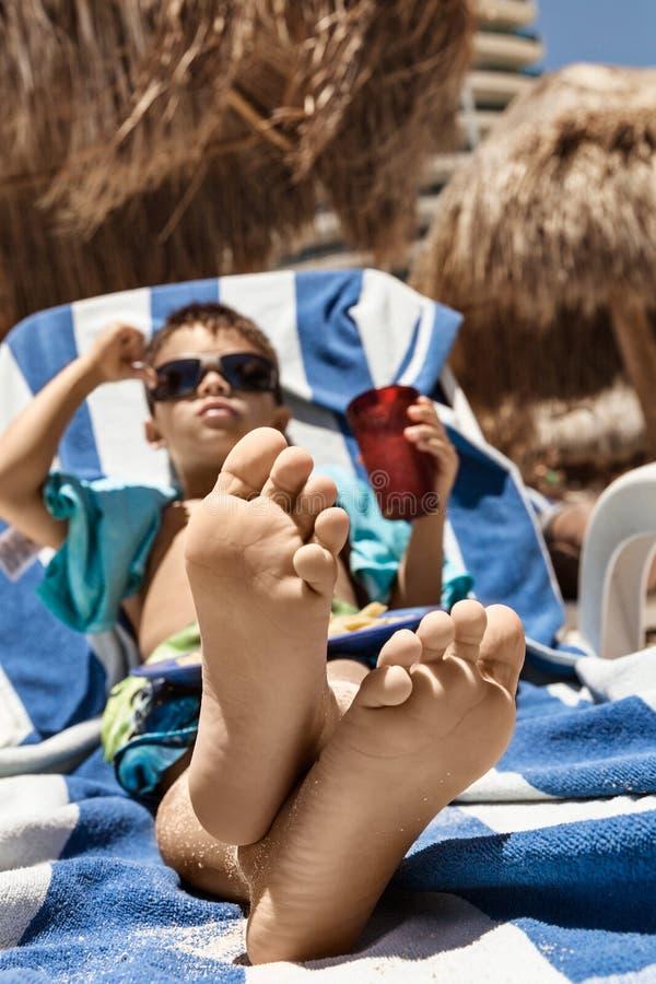 Lyckligt barn som kopplar av på stranden med hans korsade fot och kläder royaltyfri fotografi