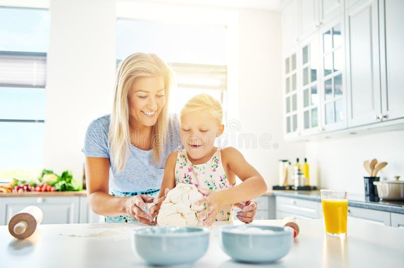 Lyckligt barn som lär att baka med hennes moder royaltyfria foton