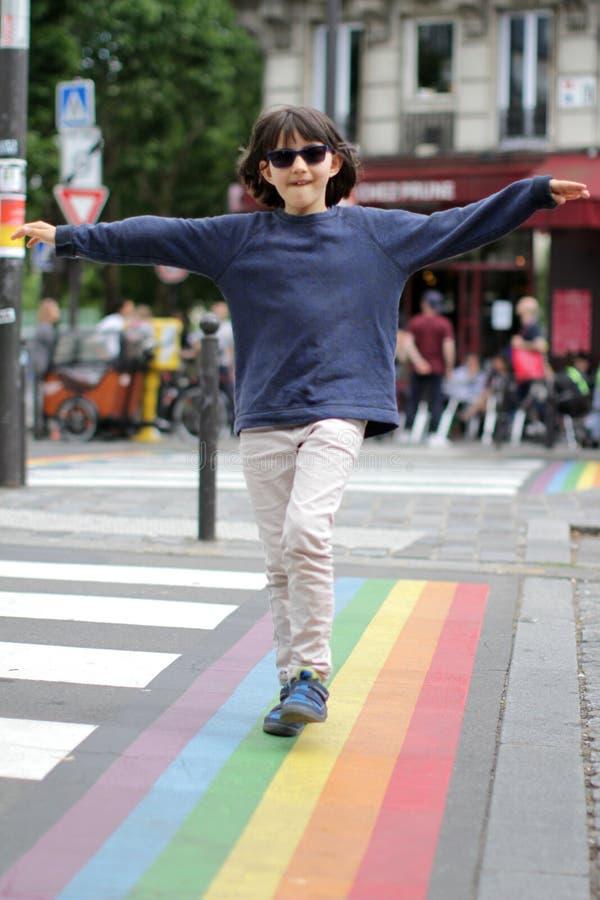 Lyckligt barn som promenerar de glade regnbågelinjerna, kafébakgrund royaltyfri bild