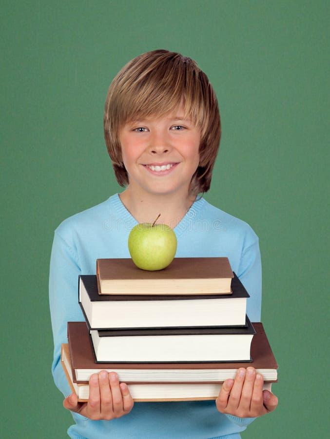 Lyckligt barn som rymmer böcker och ett äpple arkivbild