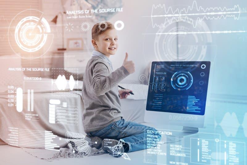 Lyckligt barn som sätter upp hans tumme, medan sitta framme av hans dator fotografering för bildbyråer