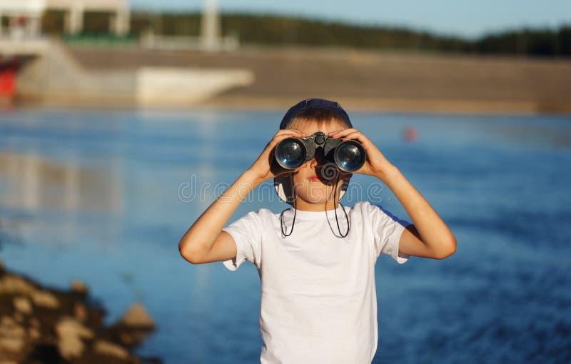 Lyckligt barn som ser i nautisk kikare mot bakgrund för blått vatten Unge som har gyckel på naturen Sommarhavsdröm och imaginat fotografering för bildbyråer