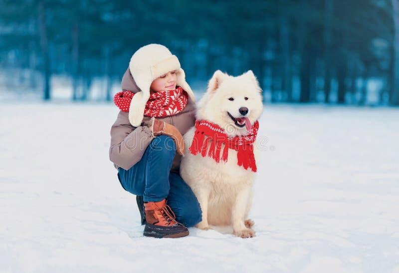 Lyckligt barn som sitter med hans vita Samoyedhund i vinterdag royaltyfria bilder