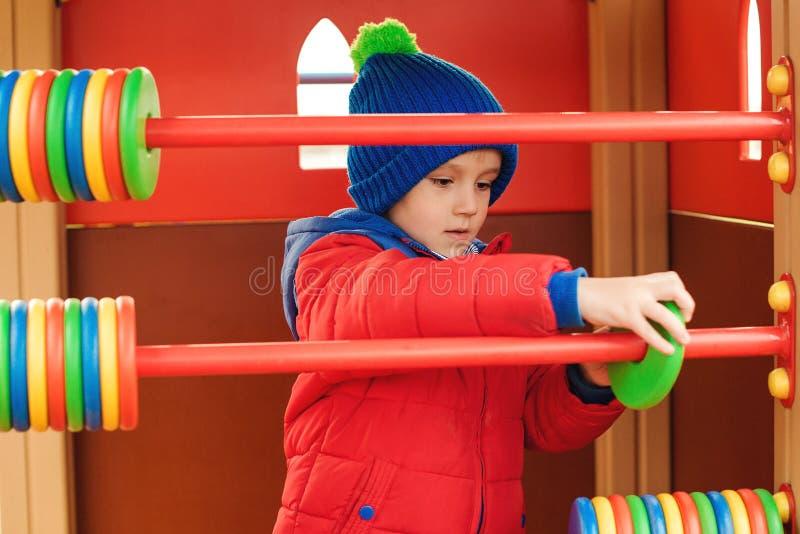Lyckligt barn som spelar lekar på färgrik lekplats Rolig unge som har gyckel på lekplats utomhus, på kallt väder Vinter barndom royaltyfri fotografi