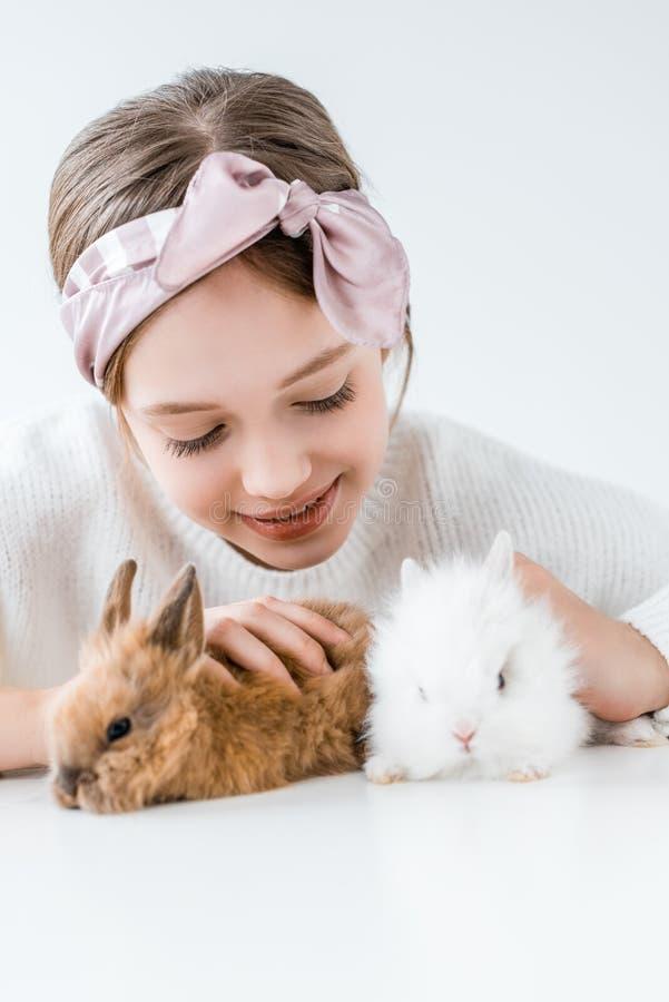Lyckligt barn som spelar med förtjusande päls- kaniner arkivfoto