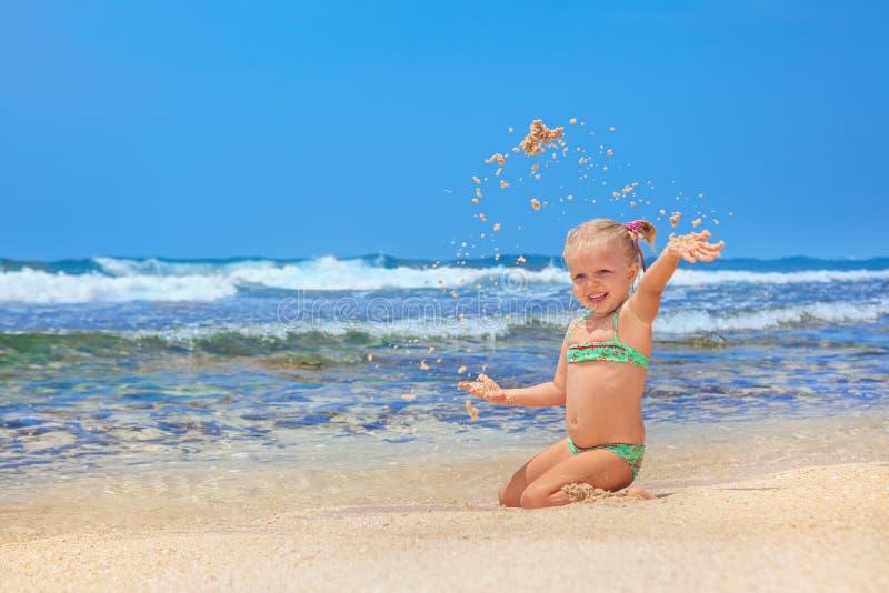 Lyckligt barn som spelar med gyckel på sandhavsstranden fotografering för bildbyråer