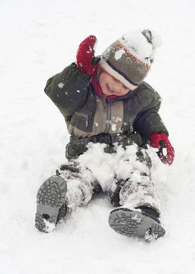 Lyckligt barn som spelar med insnöad vinter royaltyfria bilder