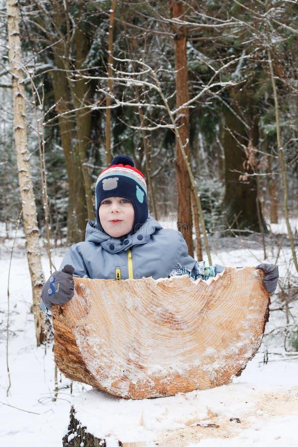 Lyckligt barn som spelar med stycket av trä i skogen i vinter royaltyfria bilder