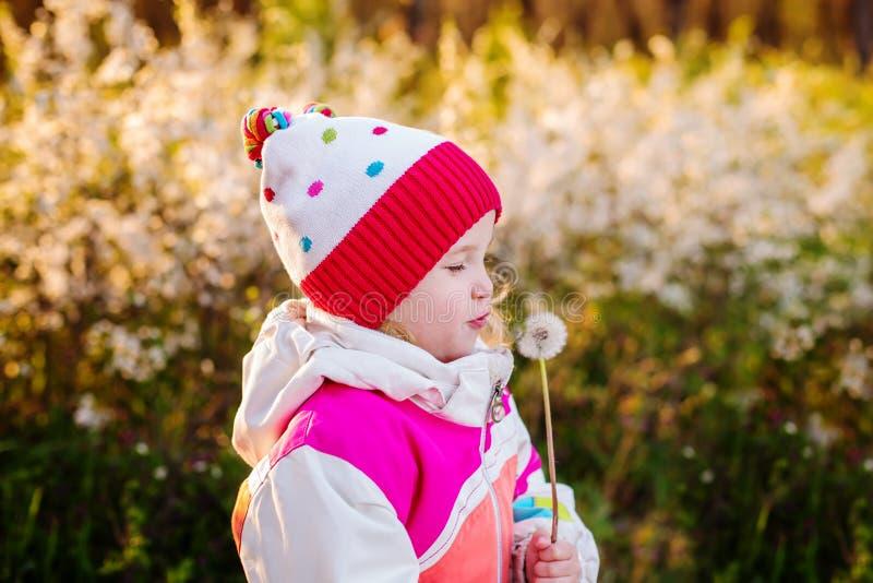 Lyckligt barn som utomhus blåser maskrosen arkivfoton