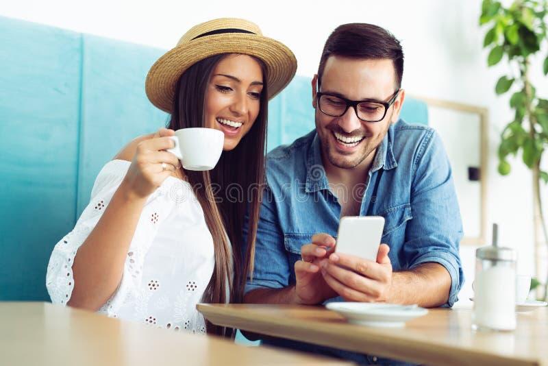 Lyckligt barnparsammanträde på kafétabellen som dricker kaffe och ser mobiltelefonen royaltyfri bild