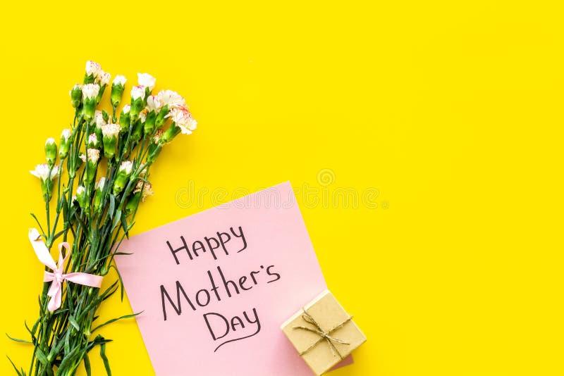 Lyckligt begrepp för dag för moder` s Handbokstäver nära bukett av den rosa nejlika- och gåvaasken på bästa sikt för gul bakgrund arkivfoto