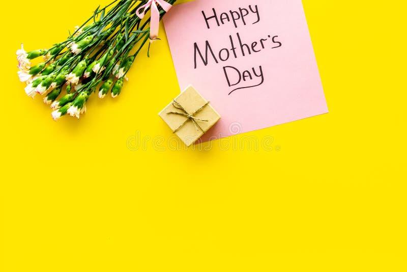 Lyckligt begrepp för dag för moder` s Handbokstäver nära bukett av den rosa nejlika- och gåvaasken på bästa sikt för gul bakgrund arkivfoton