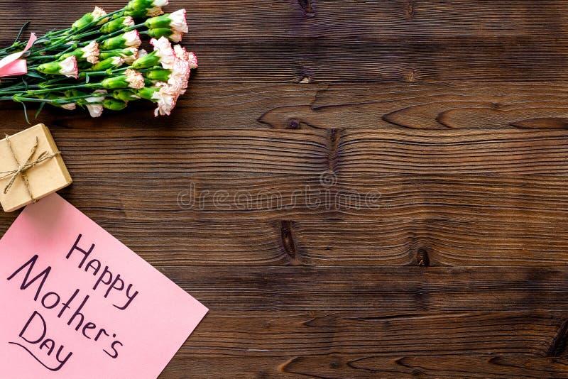 Lyckligt begrepp för dag för moder` s Handbokstäver nära bukett av den rosa nejlika- och gåvaasken på mörk träbakgrundsöverkant royaltyfri fotografi