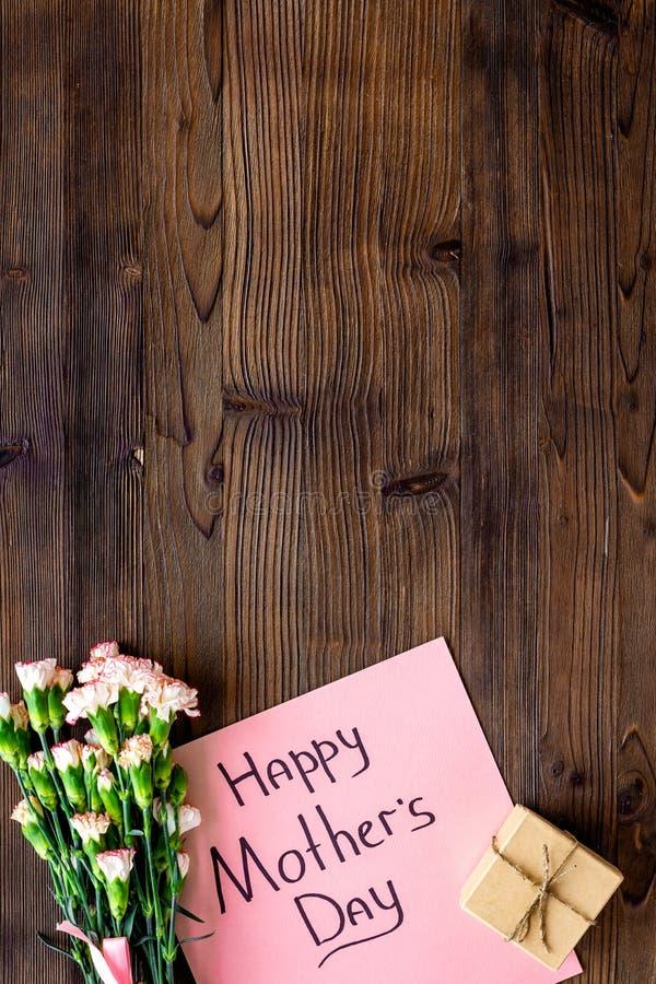 Lyckligt begrepp för dag för moder` s Handbokstäver nära bukett av den rosa nejlika- och gåvaasken på mörk träbakgrundsöverkant fotografering för bildbyråer