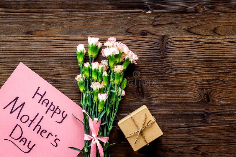 Lyckligt begrepp för dag för moder` s Handbokstäver nära bukett av den rosa nejlika- och gåvaasken på mörk träbakgrundsöverkant royaltyfria foton