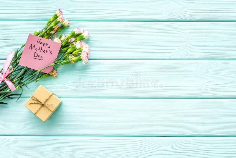 Lyckligt begrepp för dag för moder` s Handbokstäver nära bukett av den rosa nejlika- och gåvaasken på träblå turkos arkivbilder
