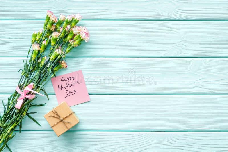 Lyckligt begrepp för dag för moder` s Handbokstäver nära bukett av den rosa nejlika- och gåvaasken på träblå turkos royaltyfria bilder
