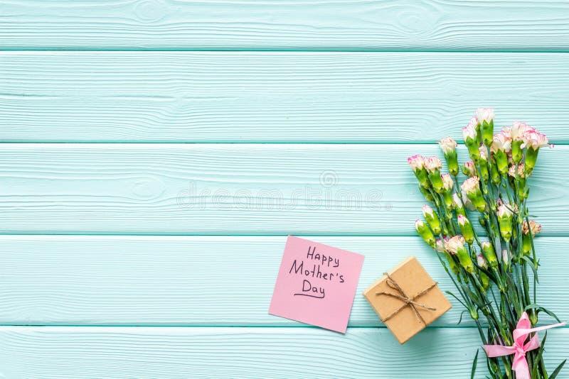 Lyckligt begrepp för dag för moder` s Handbokstäver nära bukett av den rosa nejlika- och gåvaasken på träblå turkos royaltyfri fotografi