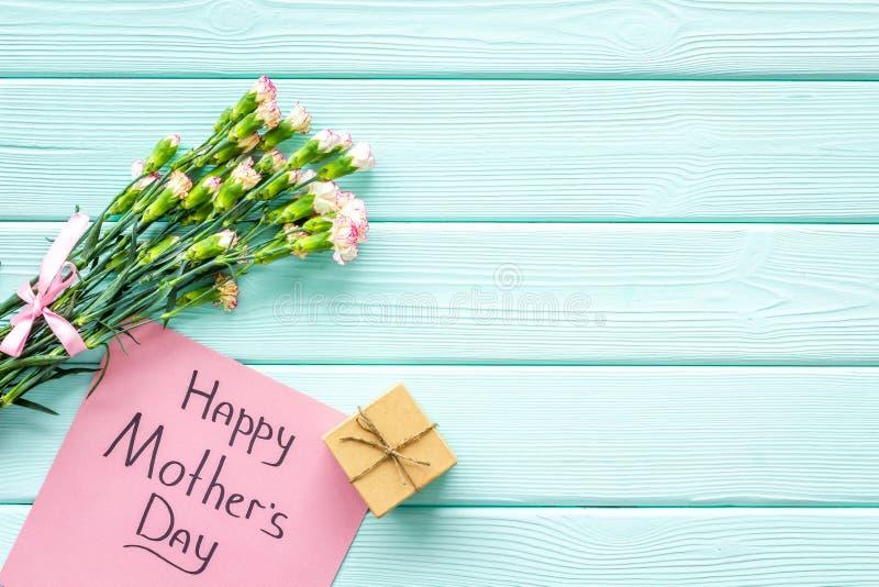 Lyckligt begrepp för dag för moder` s Handbokstäver nära bukett av den rosa nejlika- och gåvaasken på träblå turkos royaltyfri foto