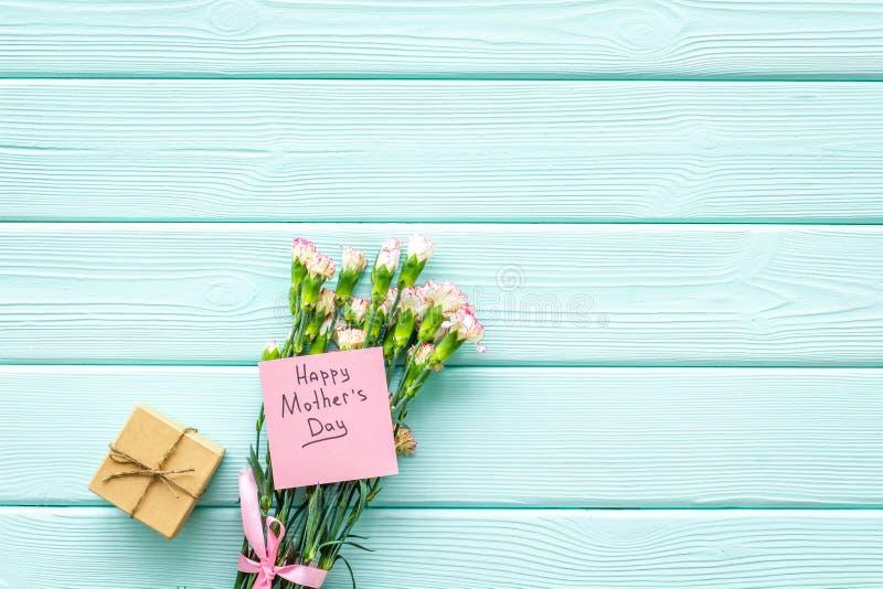 Lyckligt begrepp för dag för moder` s Handbokstäver nära bukett av den rosa nejlika- och gåvaasken på träblå turkos royaltyfri bild