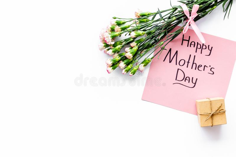 Lyckligt begrepp för dag för moder` s Handbokstäver nära bukett av den rosa nejlika- och gåvaasken på den vita kopian för bästa s royaltyfri foto
