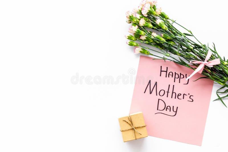 Lyckligt begrepp för dag för moder` s Handbokstäver nära bukett av den rosa nejlika- och gåvaasken på den vita kopian för bästa s royaltyfri fotografi