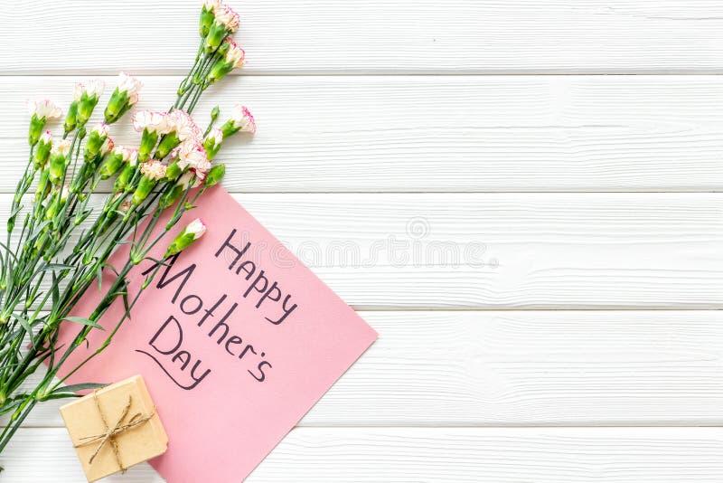 Lyckligt begrepp för dag för moder` s Handbokstäver nära bukett av den rosa nejlika- och gåvaasken på den vita träbakgrundsöverka arkivfoto