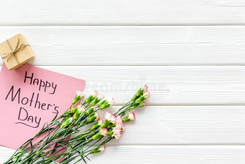 Lyckligt begrepp för dag för moder` s Handbokstäver nära bukett av den rosa nejlika- och gåvaasken på den vita träbakgrundsöverka arkivbilder