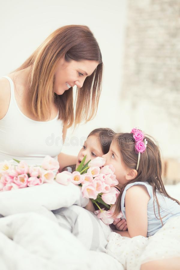 Lyckligt begrepp för dag för moder` s Mamman med unga döttrar för twocute kopplar samman på sängen i sovrummet och en bukett av b arkivbild