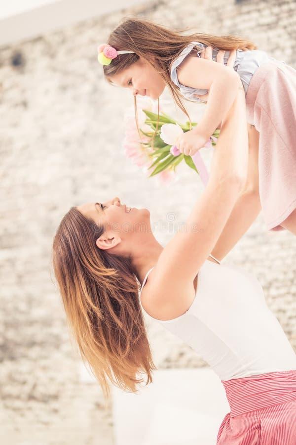Lyckligt begrepp för dag för moder` s Mamman tar hennes barn från glädje över hennes huvud arkivfoton