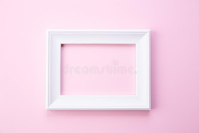 Lyckligt begrepp f?r moderdag Bästa sikt av den vita bildramen på rosa pastellfärgad bakgrund Lekmanna- l?genhet royaltyfri fotografi
