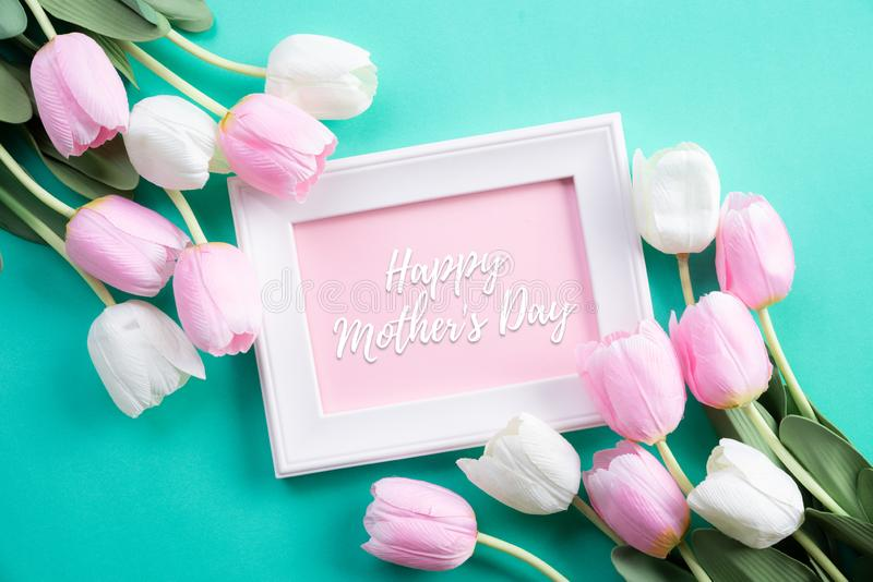 Lyckligt begrepp f?r moderdag B?sta sikt av rosa tulpanblommor och den vita bildramen med lycklig moders text f?r dag p? gr?n pas royaltyfri bild