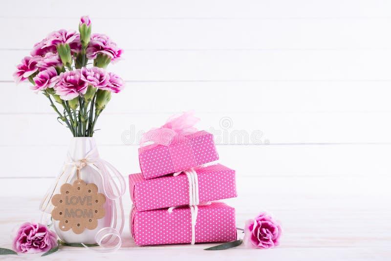 Lyckligt begrepp f?r moderdag Gåvaask med den rosa nejlikablomman på vit trätabellbakgrund arkivfoto