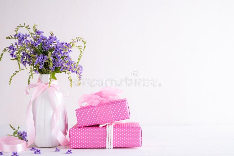 Lyckligt begrepp f?r moderdag G?vaask med den purpurf?rgade blomman p? vit tr?tabellbakgrund royaltyfria foton