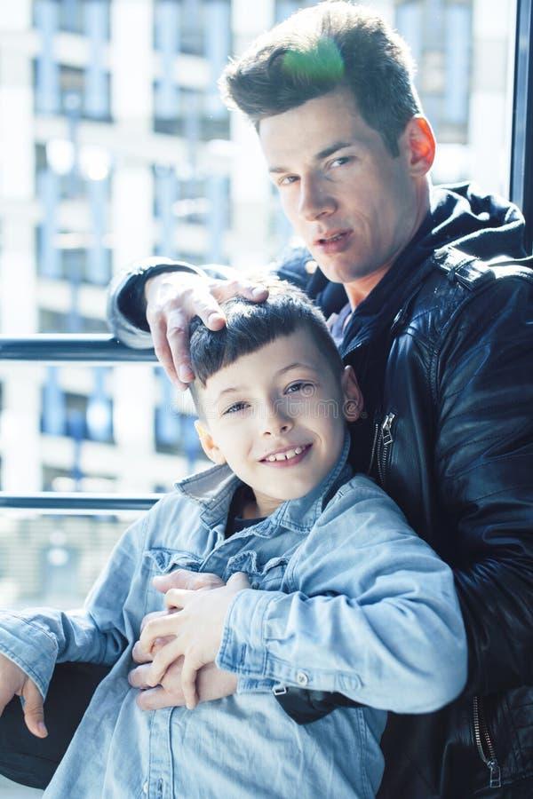 Lyckligt begrepp, fader och son för familj tillsammans på fönsterhuggings som tycker om solljus, livsstilfolk på sommar royaltyfri bild