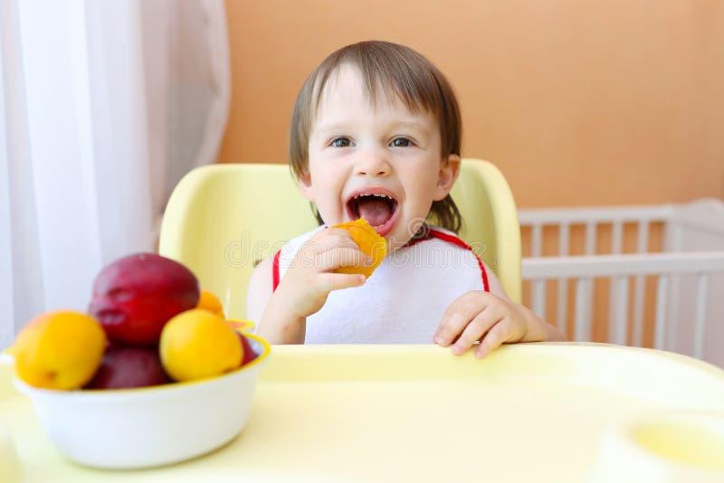 Lyckligt behandla som ett barn äta frukter royaltyfri bild