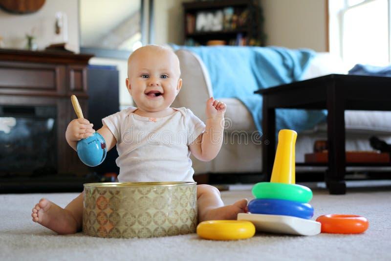 Lyckligt behandla som ett barn att spela med musikleksaker hemma arkivfoto