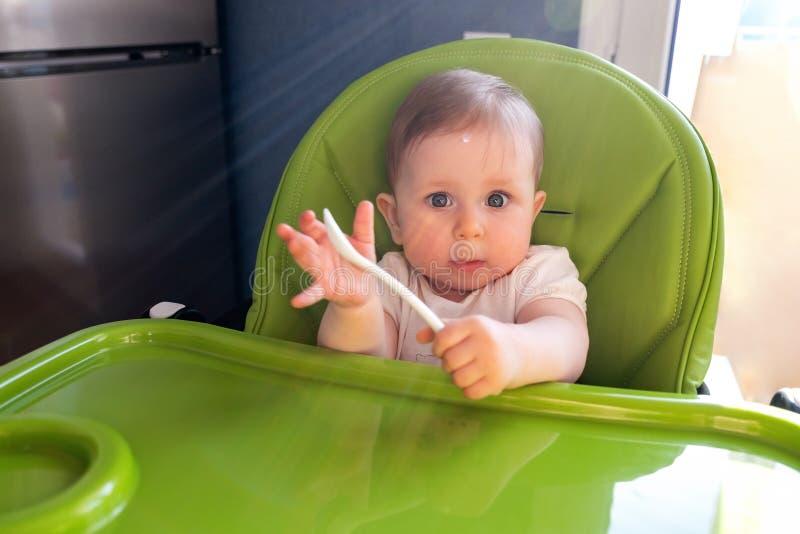 Lyckligt behandla som ett barn barnsammanträde i stol med en sked royaltyfri bild