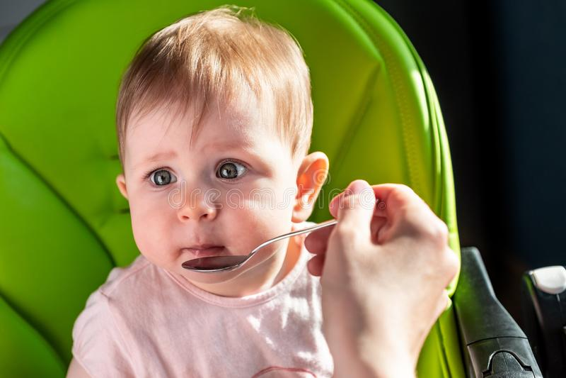 Lyckligt behandla som ett barn barnsammanträde i stol med en sked fotografering för bildbyråer