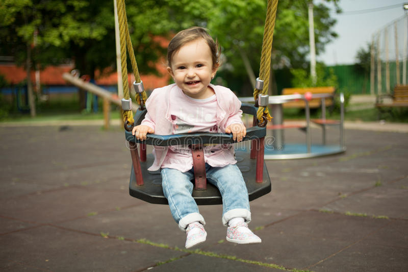 Lyckligt behandla som ett barn flickan ger sig i gunga fotografering för bildbyråer